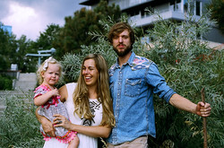 Dad, mom and little girl by a bush