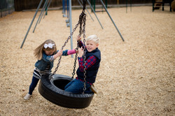 Young boy and girl with tire swing