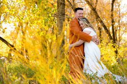 Bride and groom hugging in fall