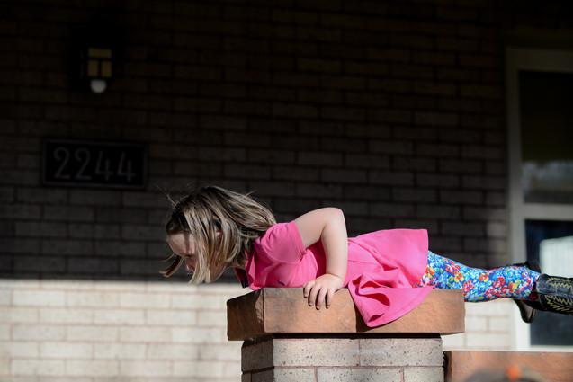 Little girl on ledge of porch