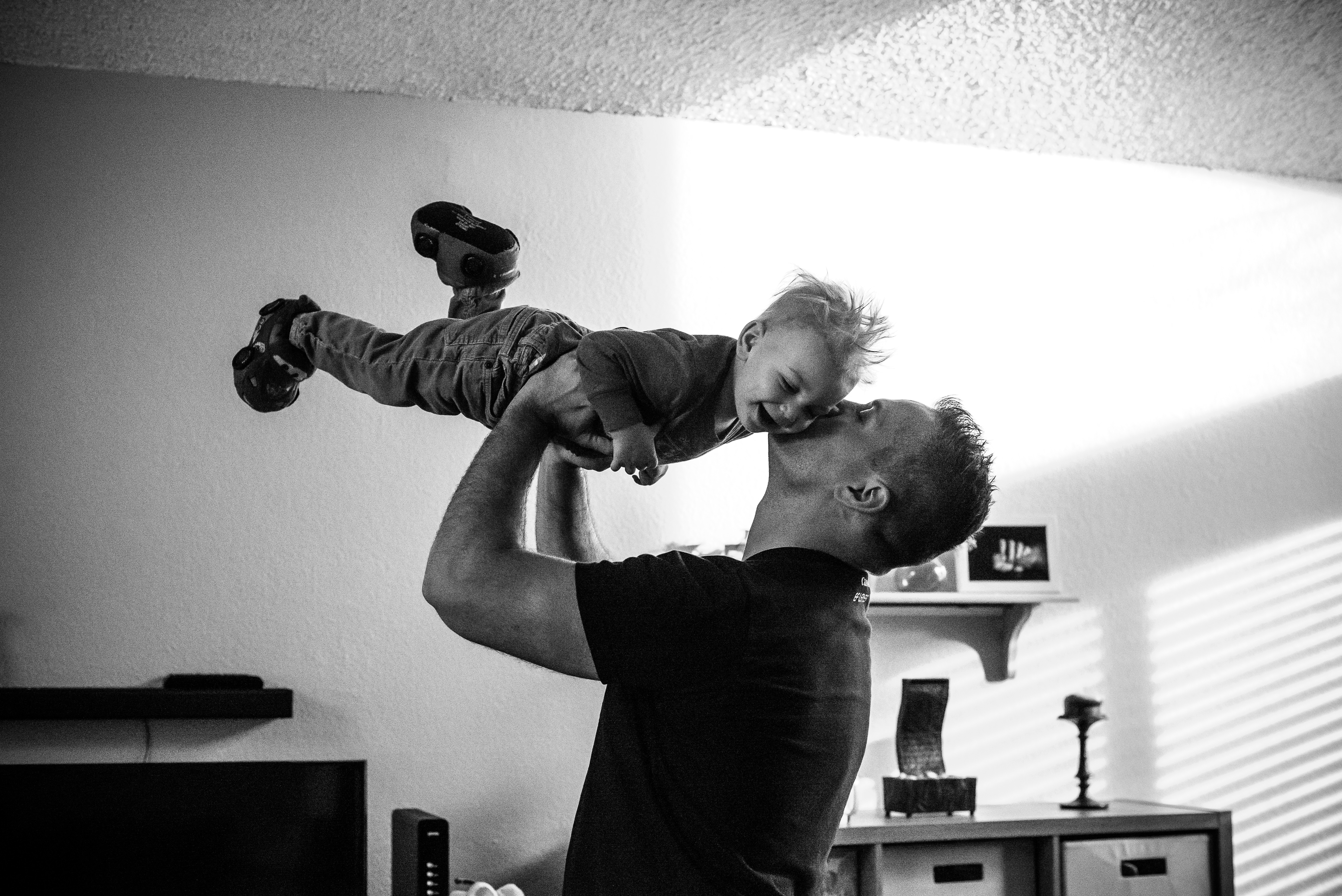 Dad lifts and kisses toddler