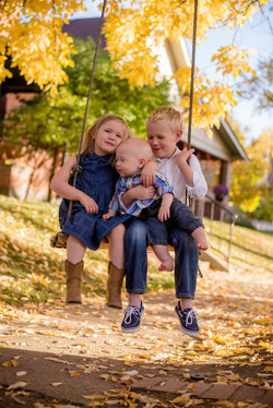 Boy, girl and baby on swing in fall