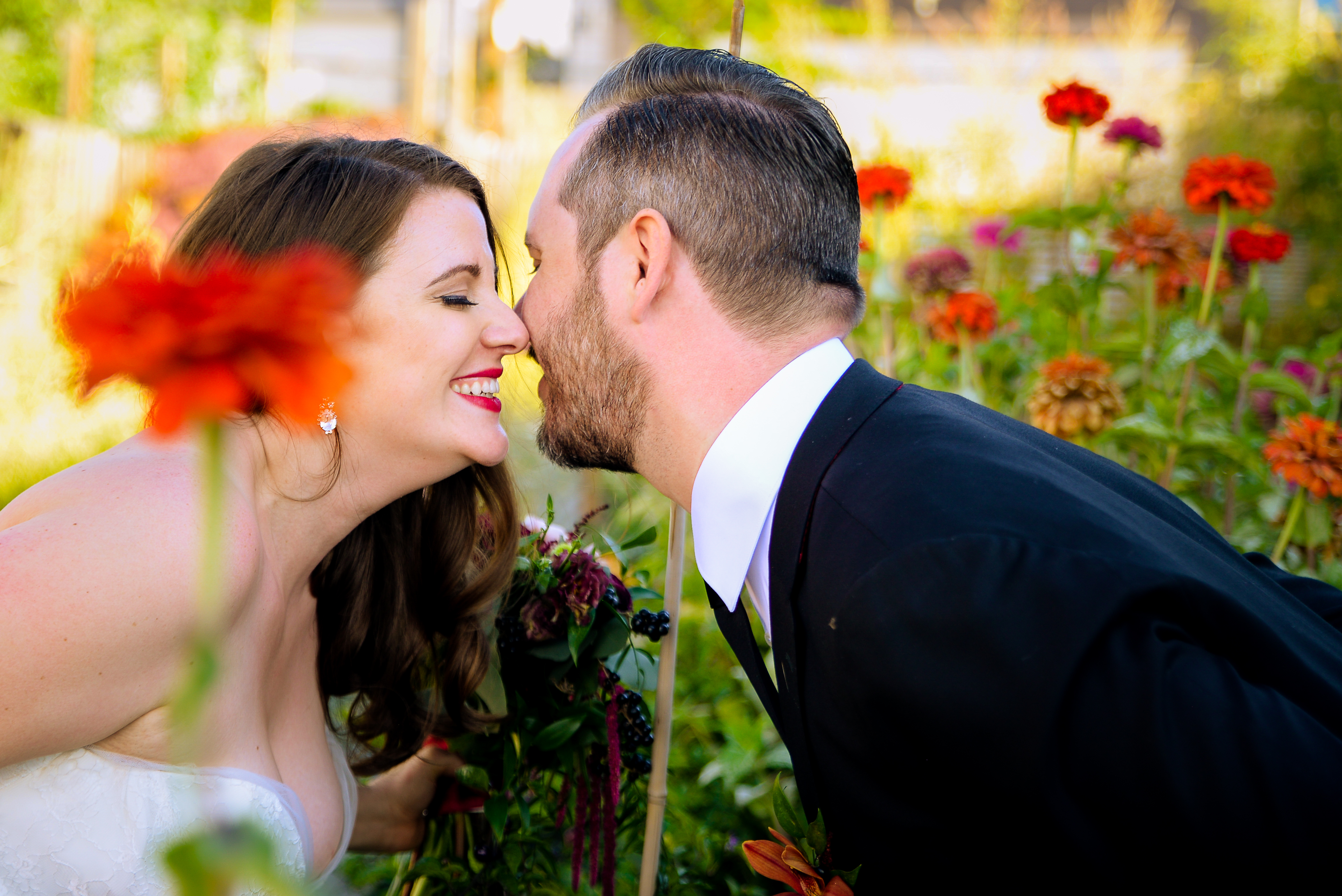 Bride and groom laughing in flowers
