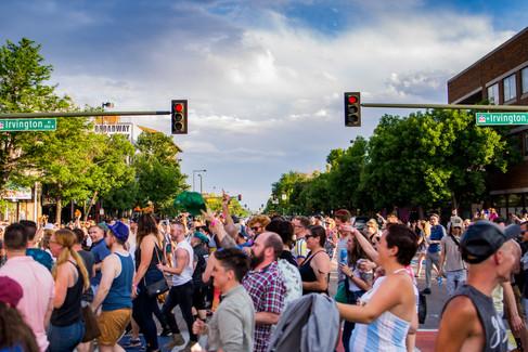 Lots of people crossing the rainbow crosswalk