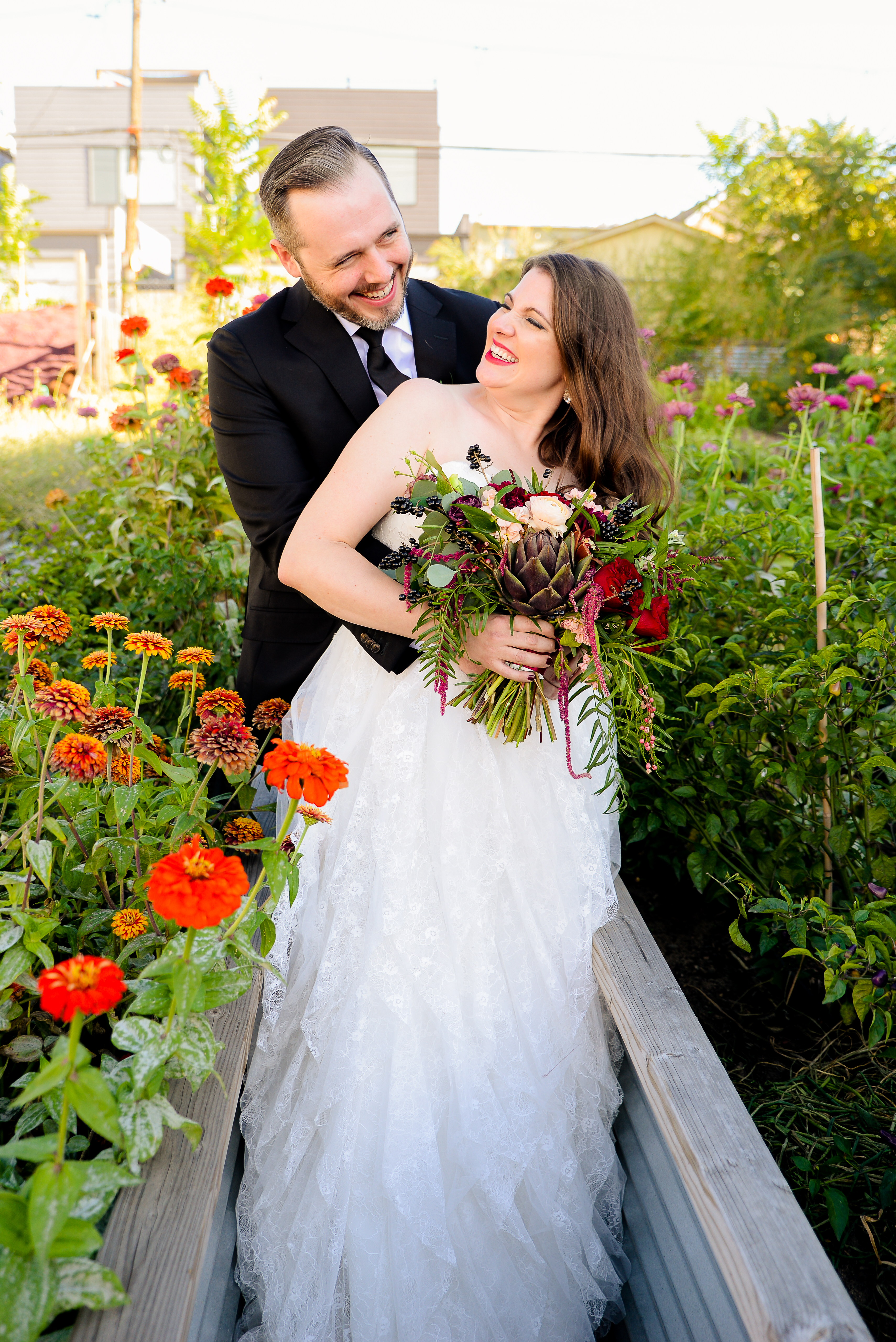 Bride and groom laughing in garden