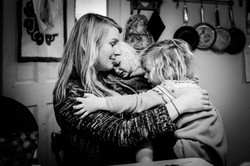 Mom hugs toddler and young daughter
