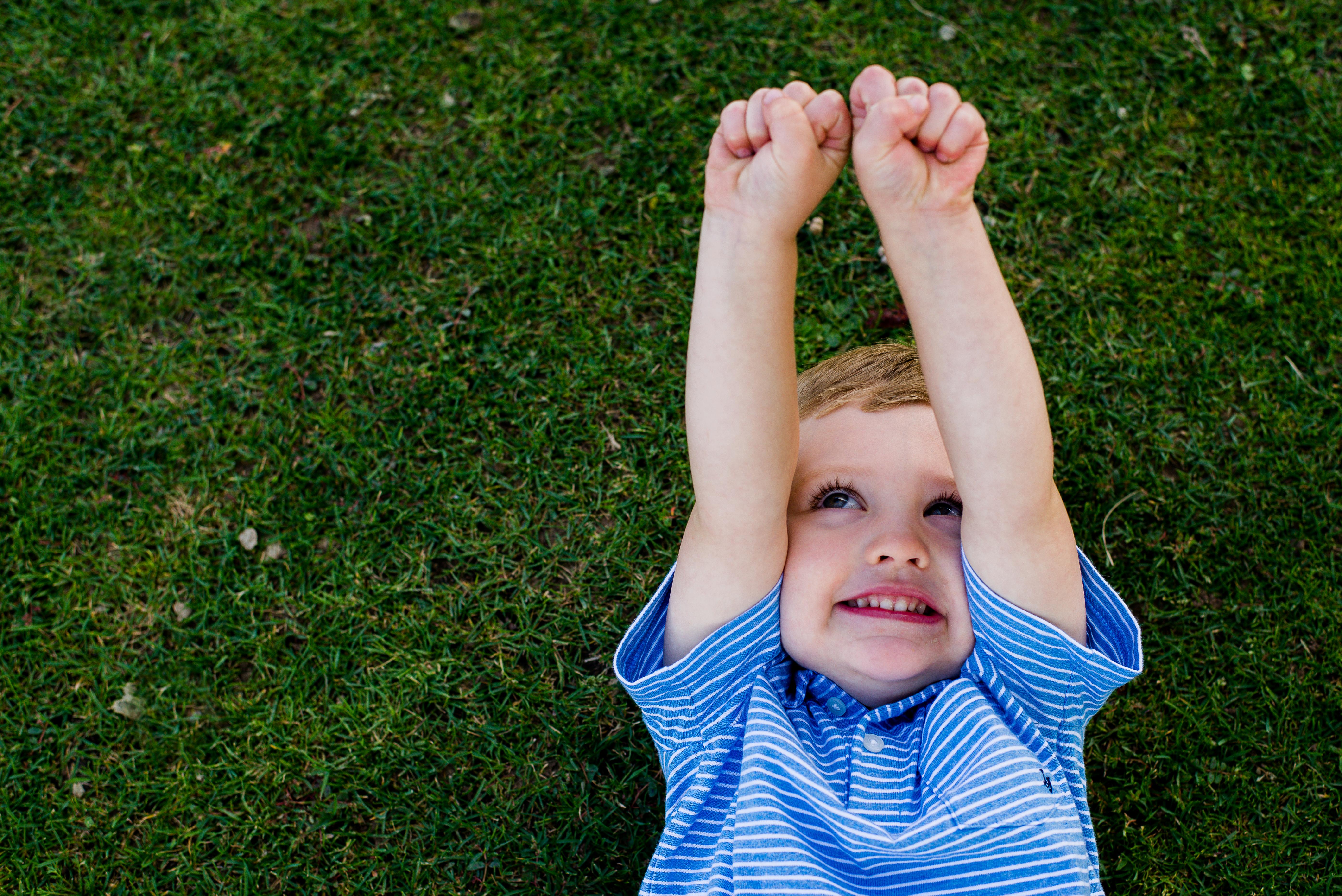 Little boy raising fists on grass
