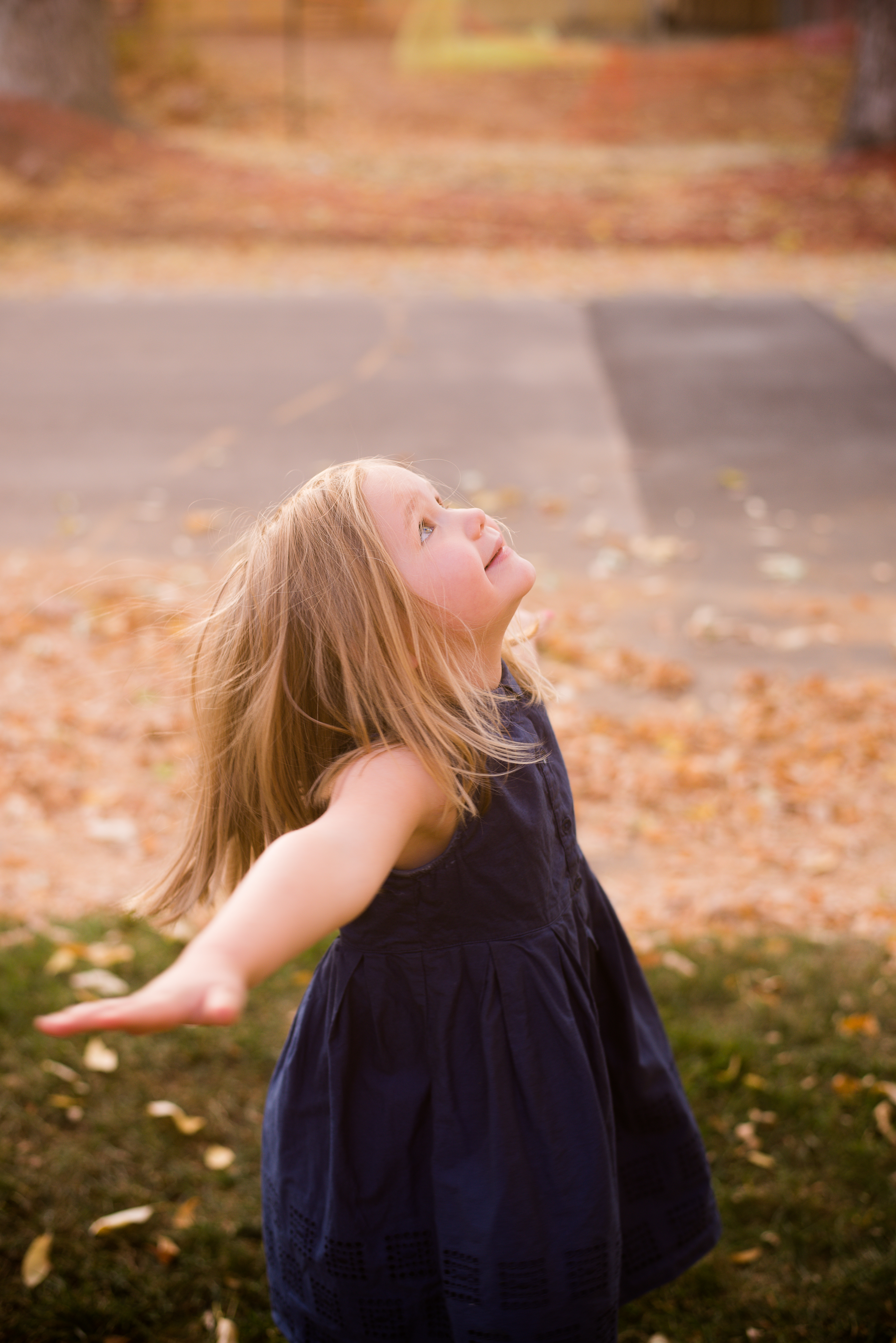 Little girl gazing up at sun in fall