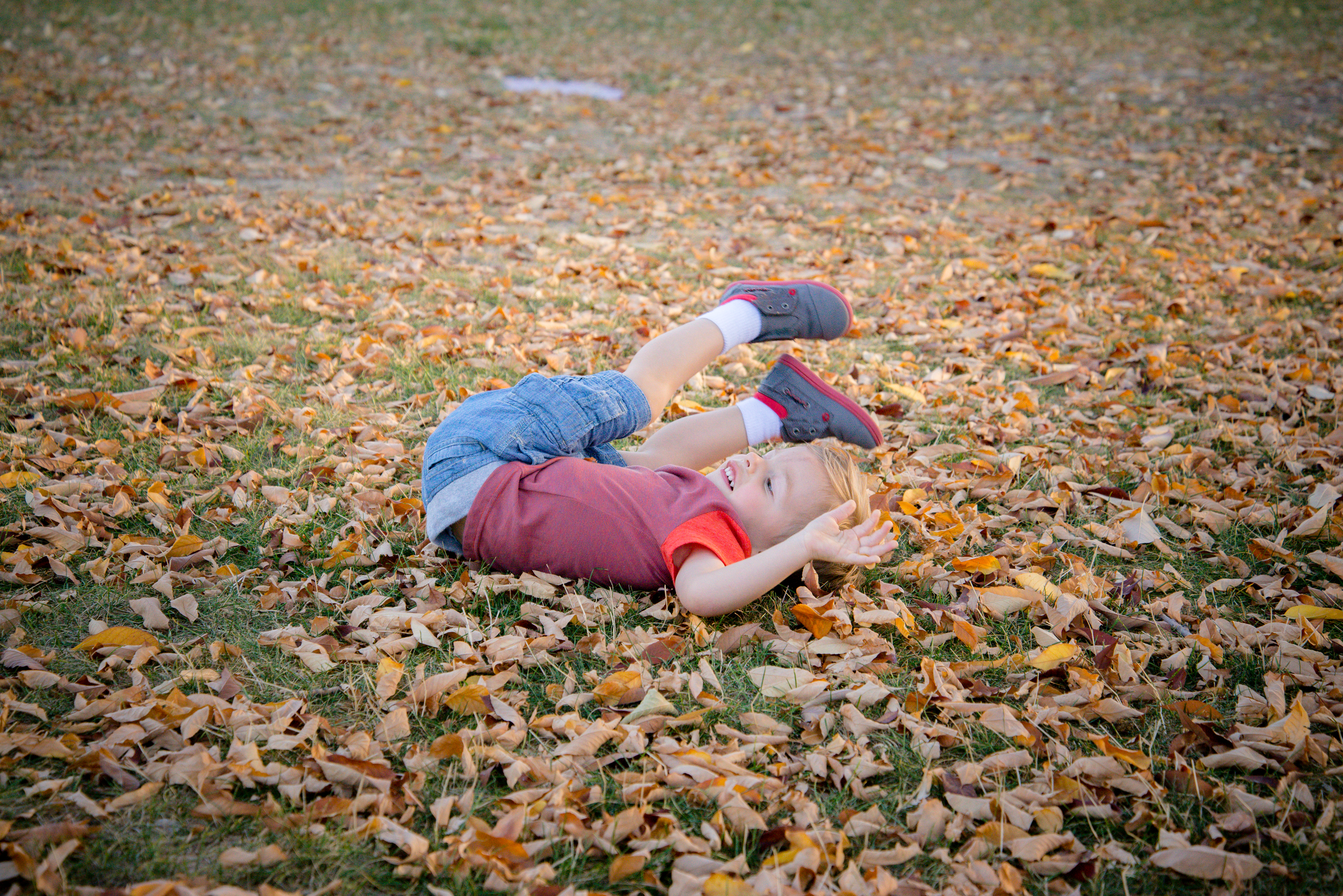 Toddler rolling in leaves