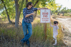 Silly dad and daughter by road sign