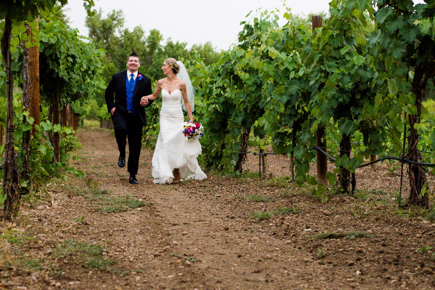 Bride and groom running in vineyard