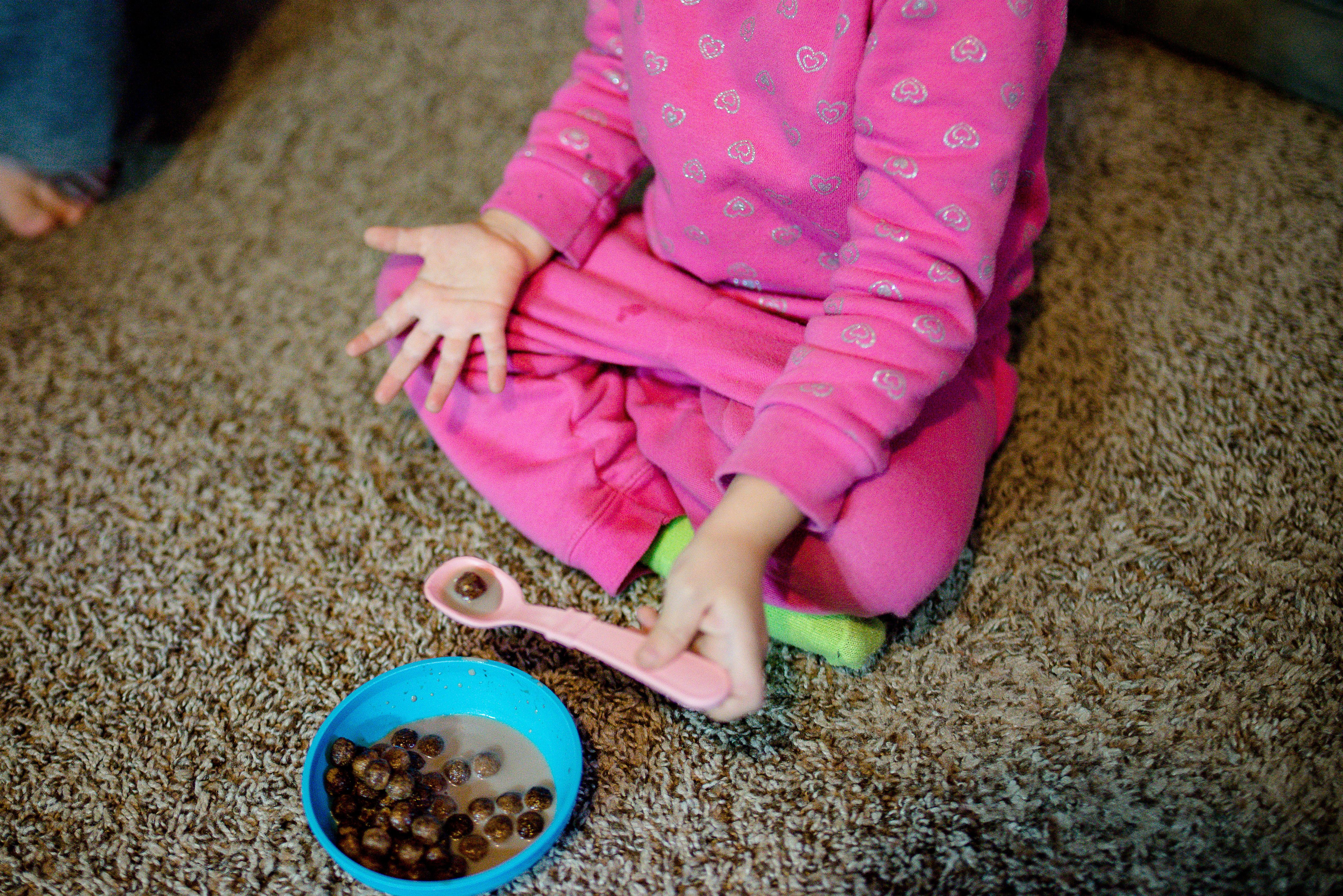 Little girl eats cereal on carpet