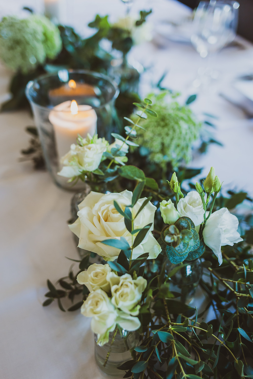 Close-up of elegant wedding reception table-setting with white flowers and green foliage, and candles in clear class jars