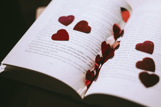 Open book with red metallic hearts lying in it