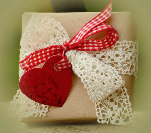 Gift wrapped in brown paper and tied with cream lace and red gingham bow and a red heart tag