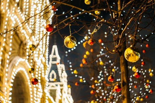 Christmas lights and decorations hanging from a tree outside a brightly lit building at night