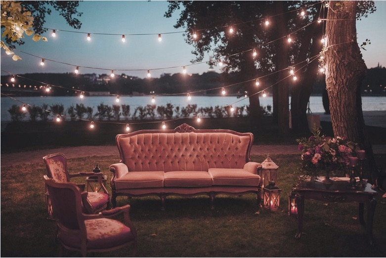 Outdoor seating area set up at outdoor wedding with plush sofa and chairs, lanterns and fairy lights strung between the trees