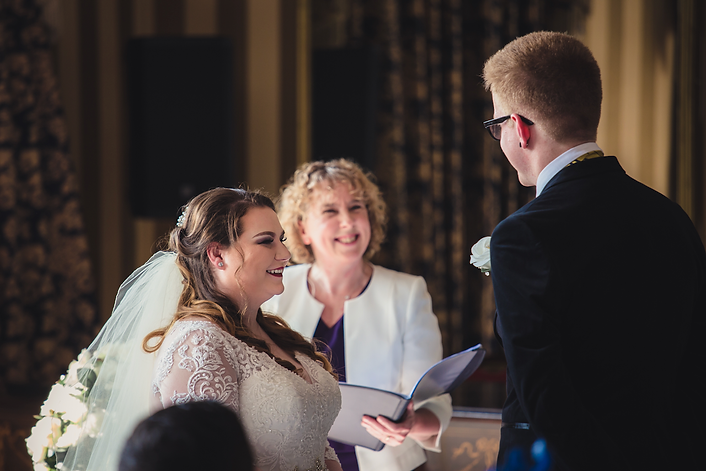 Bride in white wedding dress and groom in formal suit smiling during their bespoke wedding ceremony in luxury hotel by Tanya Jones Perfect Promises Sussex Celebrant, Surrey Celebrant, London Celebrant, UK Celebrant