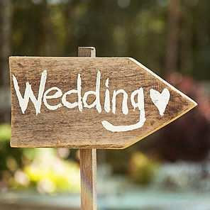 Wooden arrow sign painted with the word Wedding and a heart in white paint.  Pointing towards wedding ceremony by Tanya Jones Perfect Promises Sussex Celebrant, Surrey Celebrant, London Celebrant, UK Celebrant