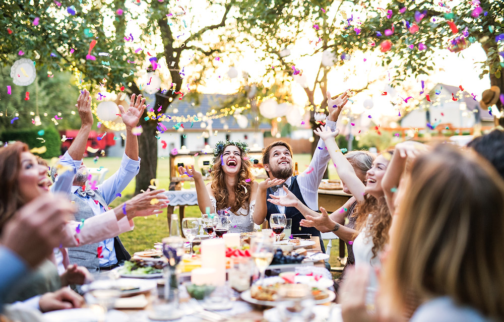 Bride and groom sitting at outside wedding reception table with friends at small wedding, with confetti in the air. Table laid with food and drink, and fairy lights strung between the trees