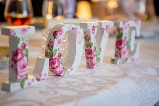 Floral letters spelling the word LOVE on a white tablecloth