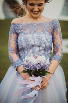 Smiling bride in lilac wedding dress with lace