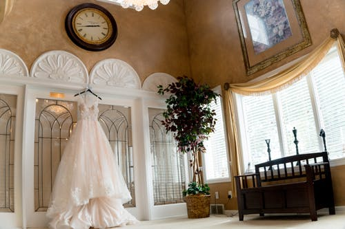 White wedding dress hanging in a bright room