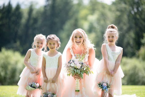 Bride and young bridesmaids smiling in the suns