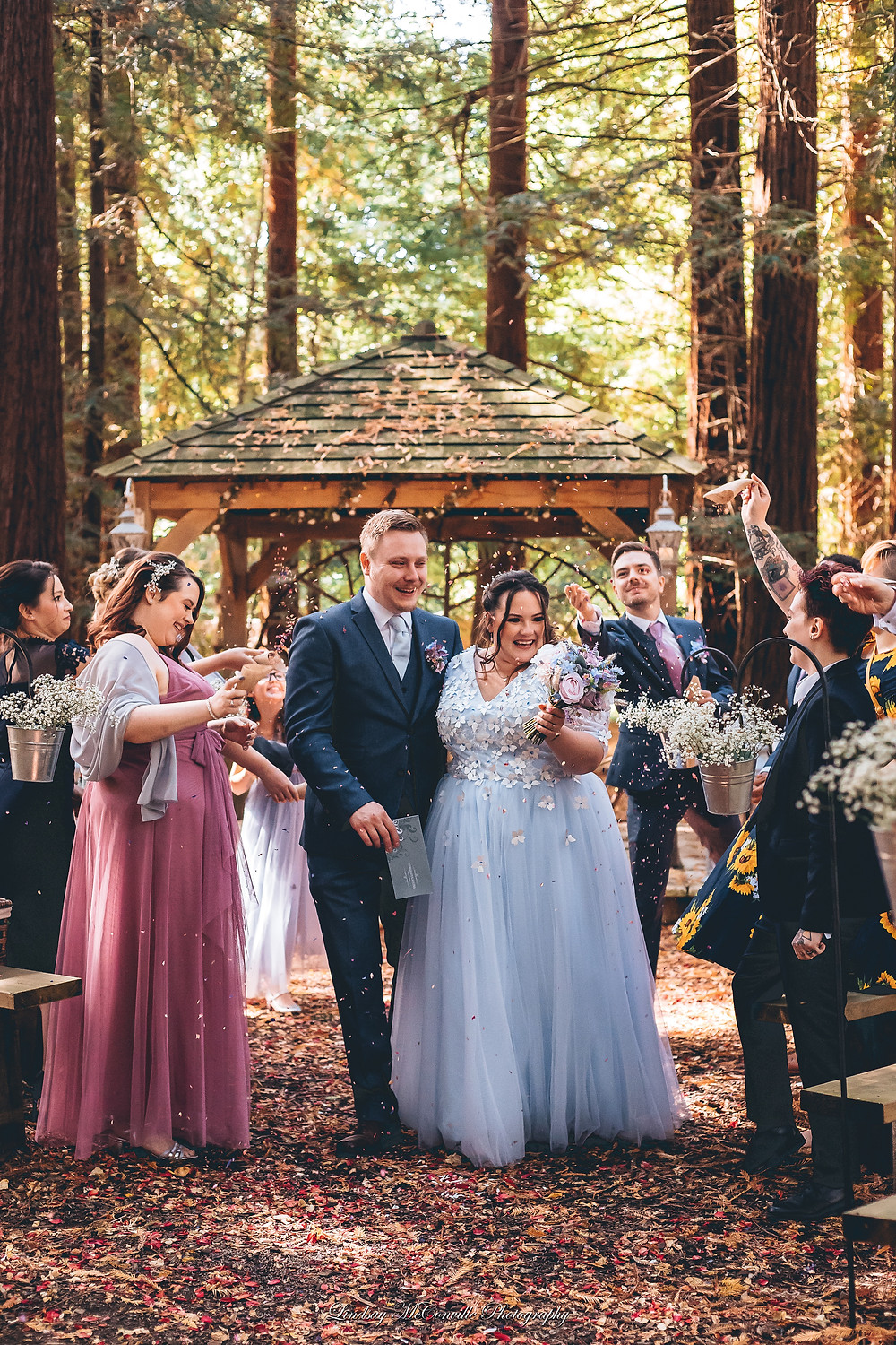 Bride in pale blue tulle and embroidered wedding dress and groom in dark suit walking through confetti thrown by bridesmaids and guests after their outdoor woodland wedding.  Tanya Jones Perfect Promises Sussex Celebrant, Surrey Celebrant, London Celebrant, UK Celebrant