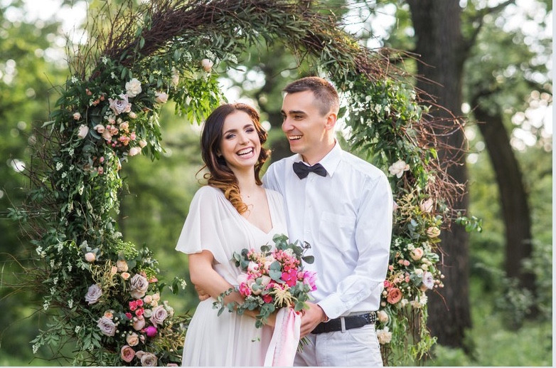 Bride in white dress with pink and white flowers in her bouquet, and groom in white shirt and black bow tie, standing in front of large hoop completely covered in flowers and foliage at their wedding ceremony.