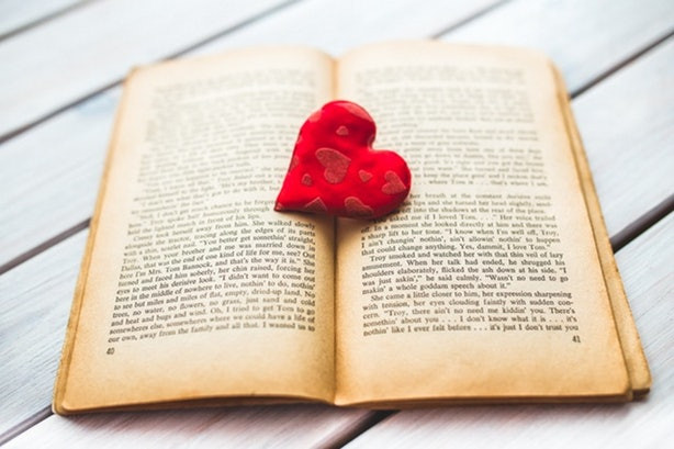 Book open with embroidered fabric heart resting on the pages