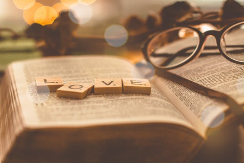 Open book with pair of glasses and scrabble letters spelling the word love
