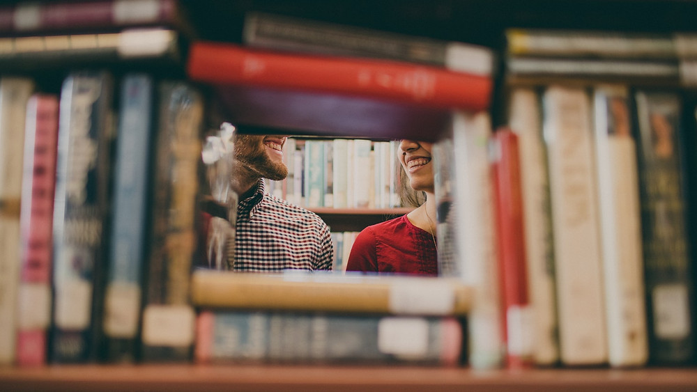 Gap in a bookshelf in a bookshop showing couple smiling at each other