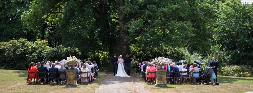 View of bride and groom standing in the shade of 400 year-old oak tree.  Guests sitting in rows watching their outdoor wedding ceremony. Tanya Jones Perfect Promises Sussex Celebrant, Surrey Celebrant, London Celebrant, UK Celebrant