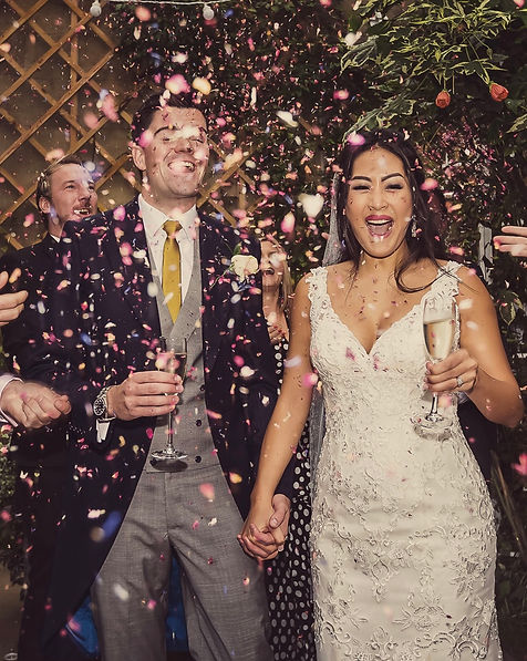 Bride in white wedding dress and groom in formal morning suit covered in confetti and holding glasses of champage, laughing after their wedding ceremony in luxury hotel by Tanya Jones Perfect Promises Sussex Celebrant and UK Celebrant