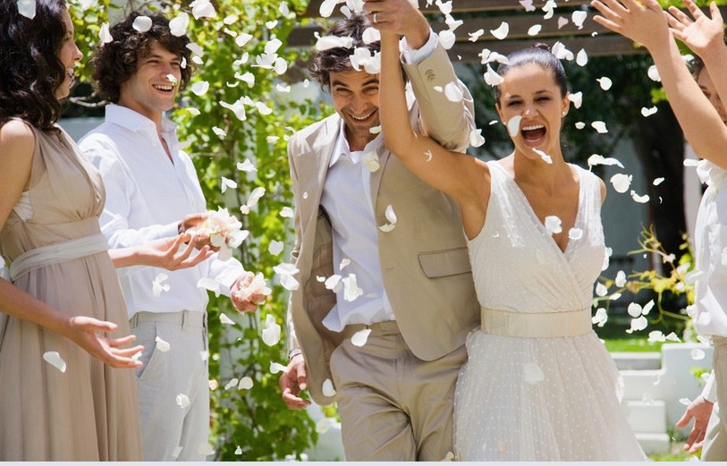 Bride in white wedding dress and groom in beige suit running through white petals thrown by bridesmaids and groomsmen after wedding ceremony. Tanya Jones Perfect Promises Sussex Celebrant, Surrey Celebrant, London Celebrant, UK Celebrant