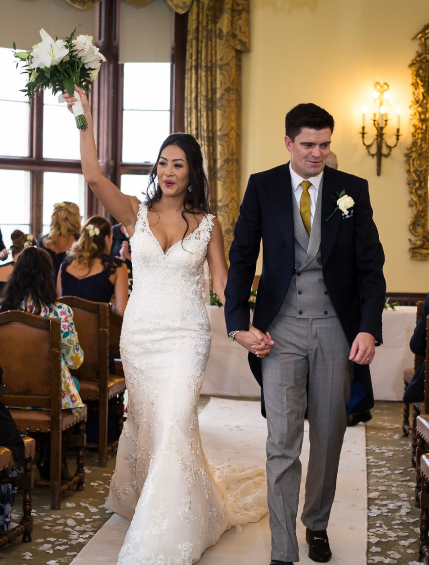 Bride in white wedding dress and groom in formal morning suit walking back down the aisle after their wedding ceremony in luxury hotel.  Bride holding her bouquet of white flowers aloft. Tanya Jones Perfect Promises Sussex Celebrant, Surrey Celebrant, London Celebrant, UK Celebrant