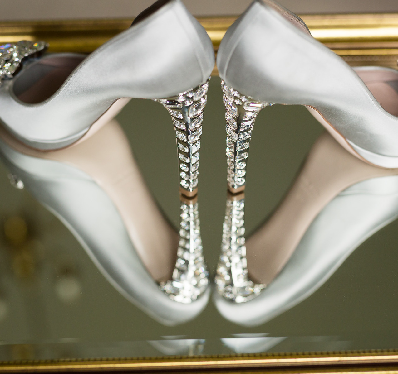 Silver Jimmy Choo wedding shoes standing on a glass tabletop