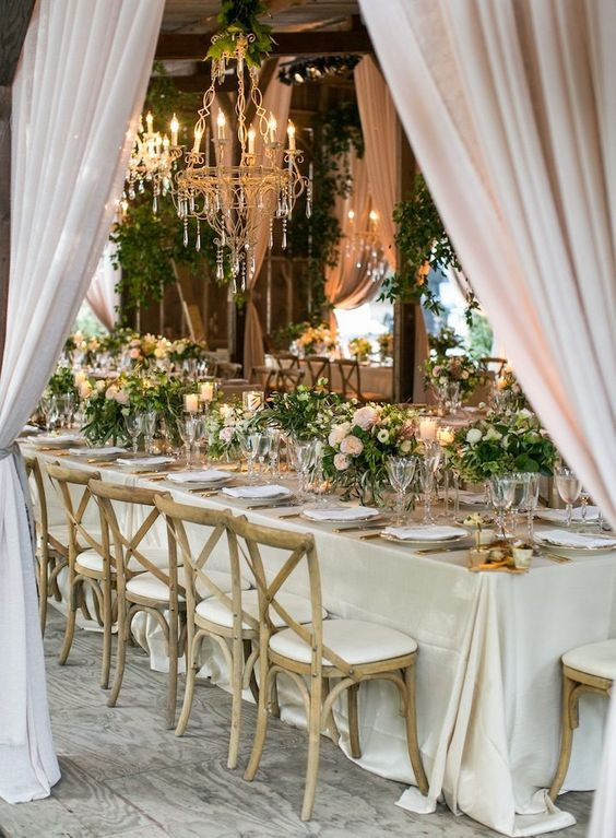 Elegant wedding reception table-setting for small wedding.  White tablecloth, clear glassware, pale pink and whit flowers.  Table surrounded by draped white voile curtains, and crystal chandelier suspended over the table