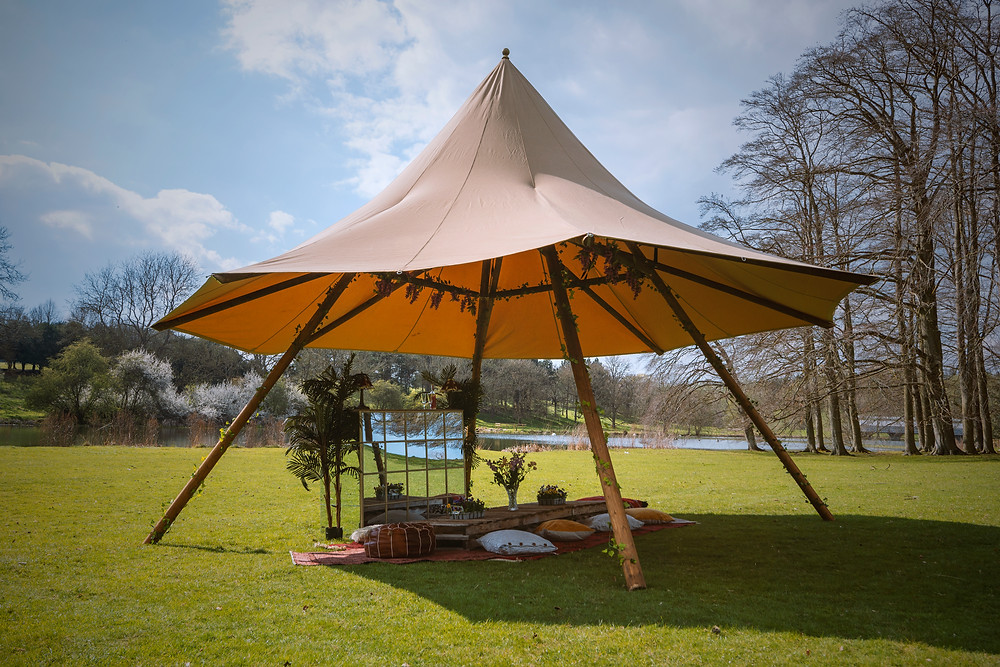 Small teepee-type tent erected on grass beside river at outdoor wedding ceremony. Seating area under the teepee with rug, cushions, and plants