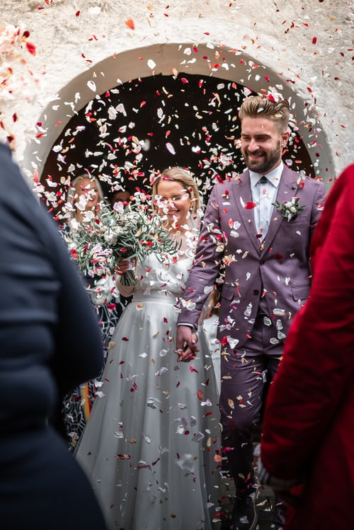 Modern bride and groom covered in confetti.  Groom wears lilac coloured suit