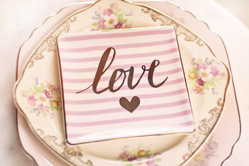 The word love printed on a square china plate sitting on floral vintage china plates