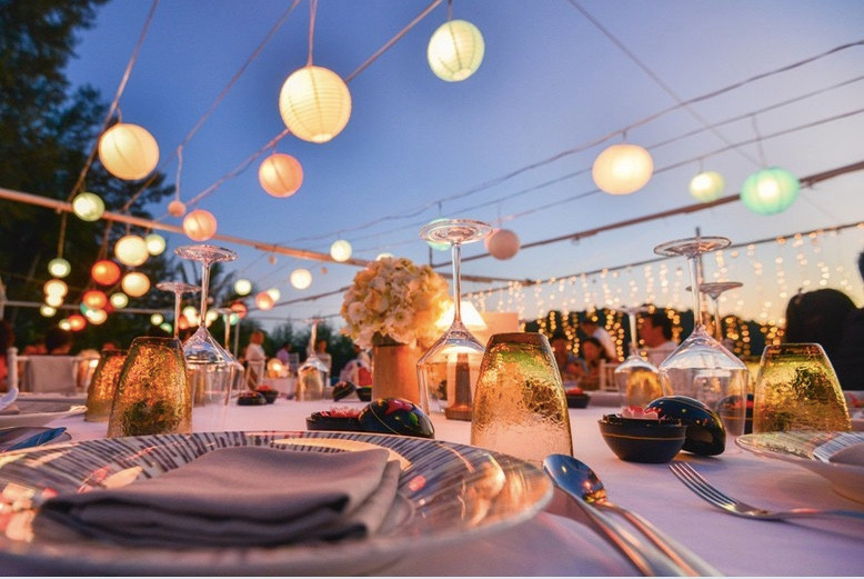 Table set for outdoor wedding reception at dusk, with amber glassware and lit paper lanterns suspended above the table