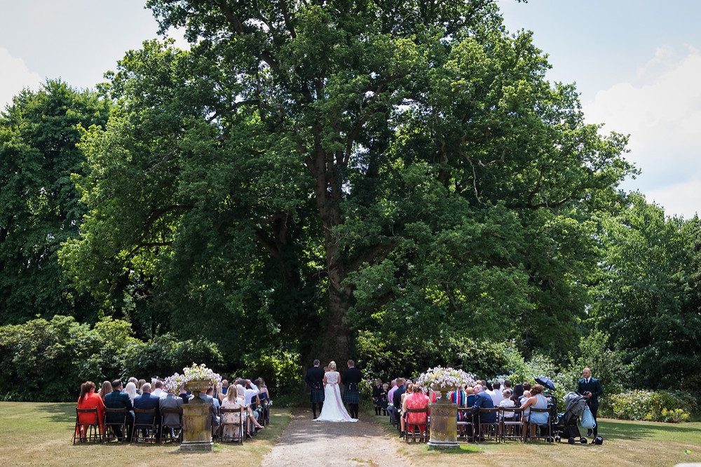 Large oak tree with celebrant wedding ceremony underneath