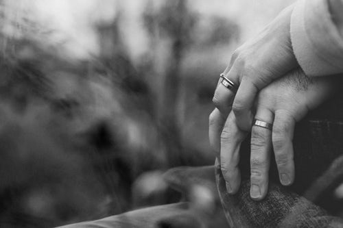 Two men's hands intertwined and showing wedding rings