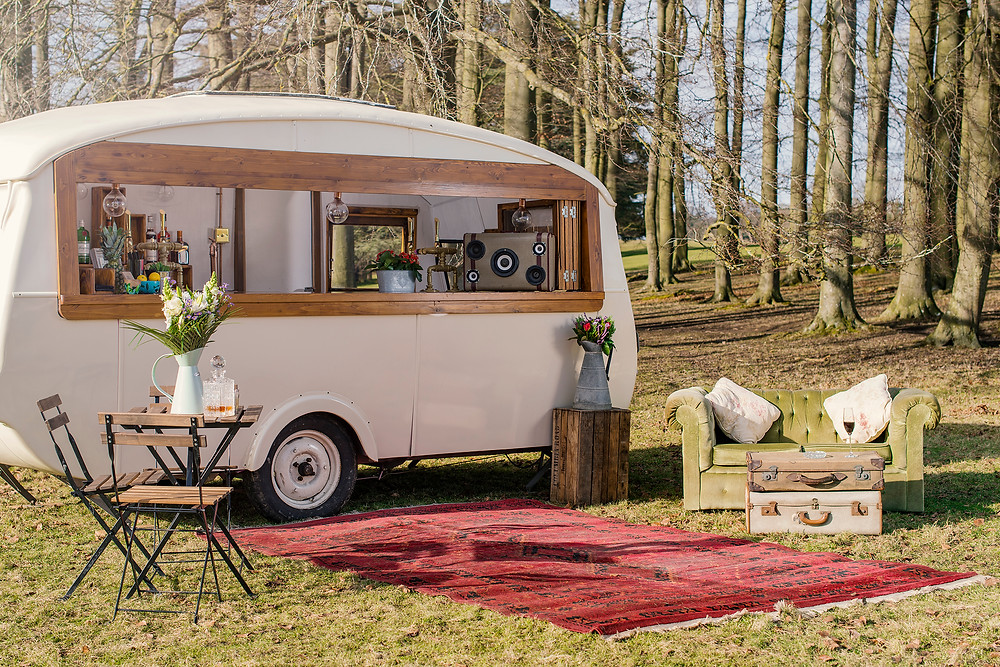Caravan set up as mobile drinks station for outdoor wedding.  Dressed with seating area with rug, table and chairs, with vase of flowers, and green sofa with old suitcases piled up as a coffee table