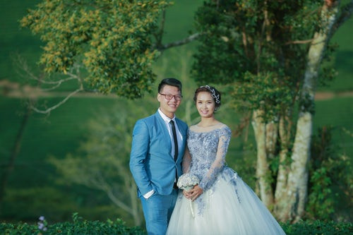 Smiling bride and groom in matching blue wedding dress and suit