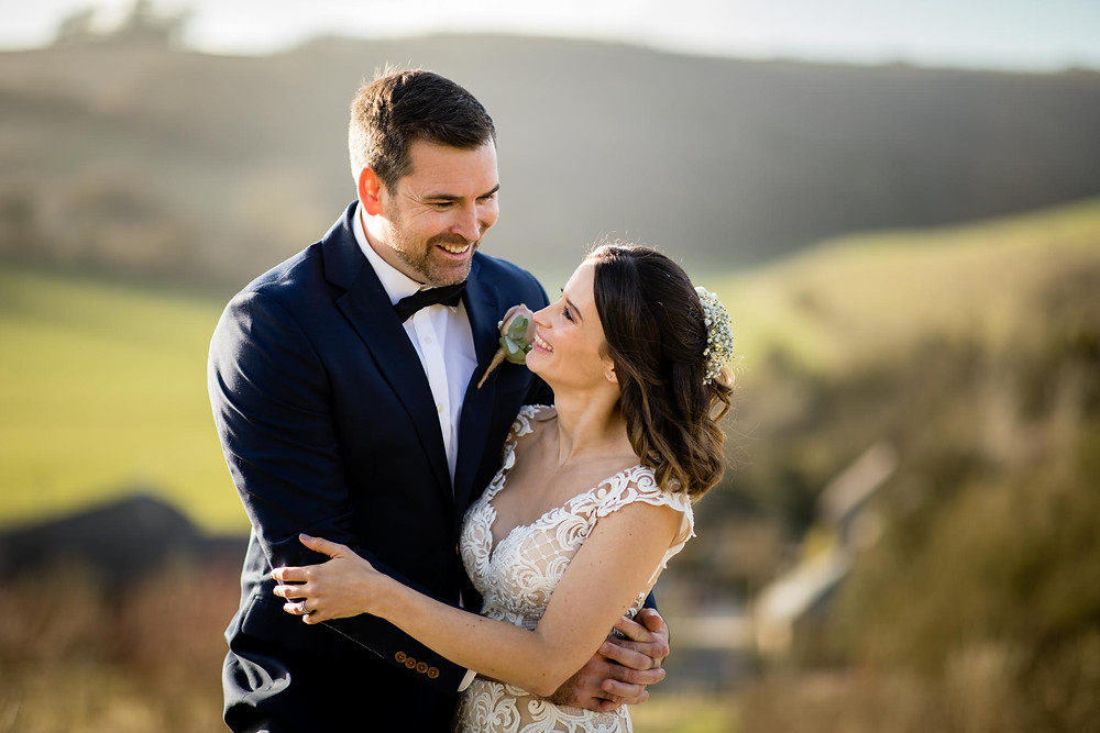 Bride in lace wedding dress and groom in dark suit and black bow tie smiling with Sussex countryside in the background. Tanya Jones Perfect Promises Sussex Celebrant, Surrey Celebrant, London Celebrant, UK Celebrant