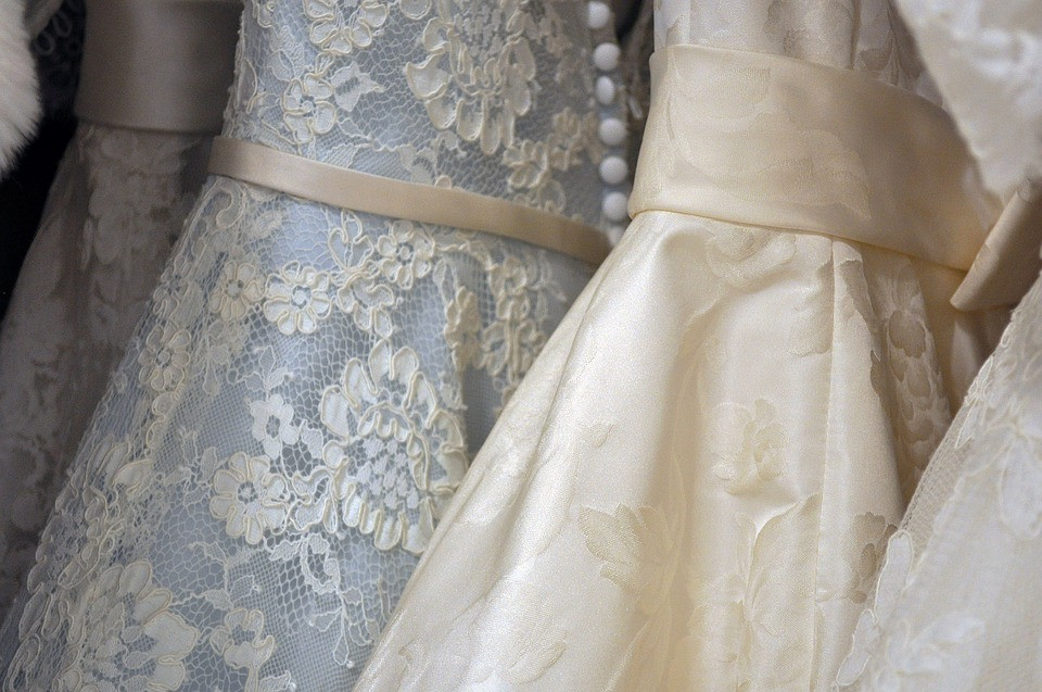 Row of ivory and pastel-coloured wedding dresses