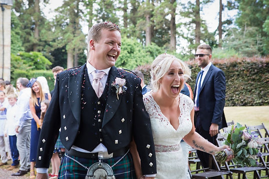 Bride in white wedding dress and groom in traditional scottish kilt covered in confetti and laughing after their outdoor wedding ceremony by Tanya Jones Perfect Promises Sussex Celebrant and UK Celebrant
